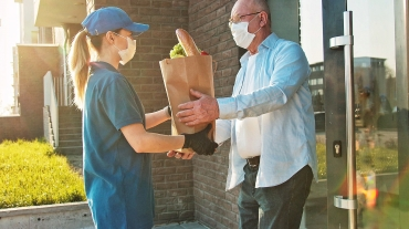 Delivery of food in quarantine. Senior man in protective mask customer receiving food bag.