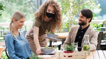 Waitress with face mask serving happy couple outdoors on terrace restaurant